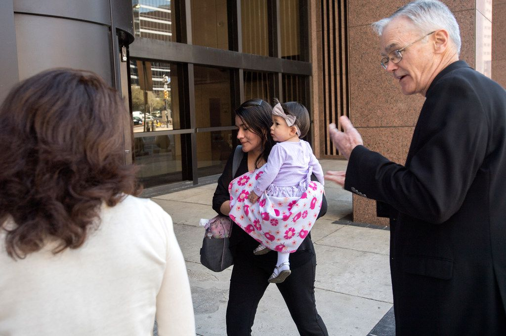 Lucia Mejia, carrying her 19-month-old daughter Teresa, is accompanied by Auxiliary Bishop Greg Kelly (right) and other supporters from her parish as she enters the Earle Cabell Federal Building to watch a video feed of a court hearing for her husband, who was detained by Immigration and Customs Enforcement.