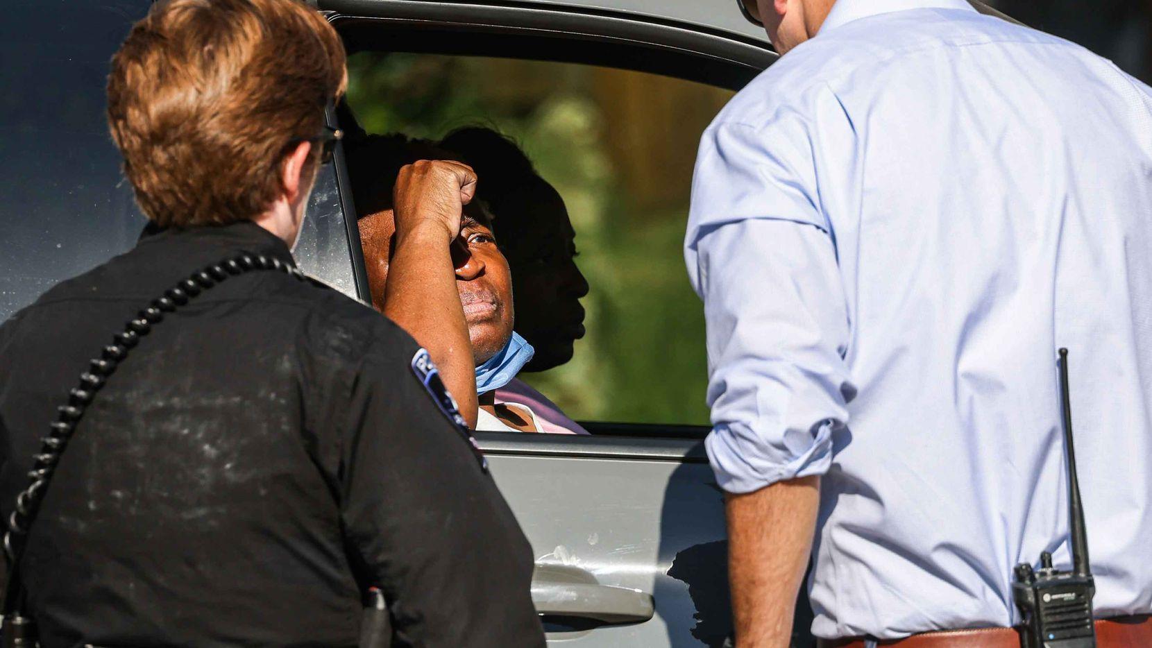 Una mujer que se negó a dar su nombre y más tarde ingresó a la casa de  Timothy George Simpkins, espera afuera del hogar mientras la policía registra el domicilio en Arlington, el 6 de octubre de 2021.
