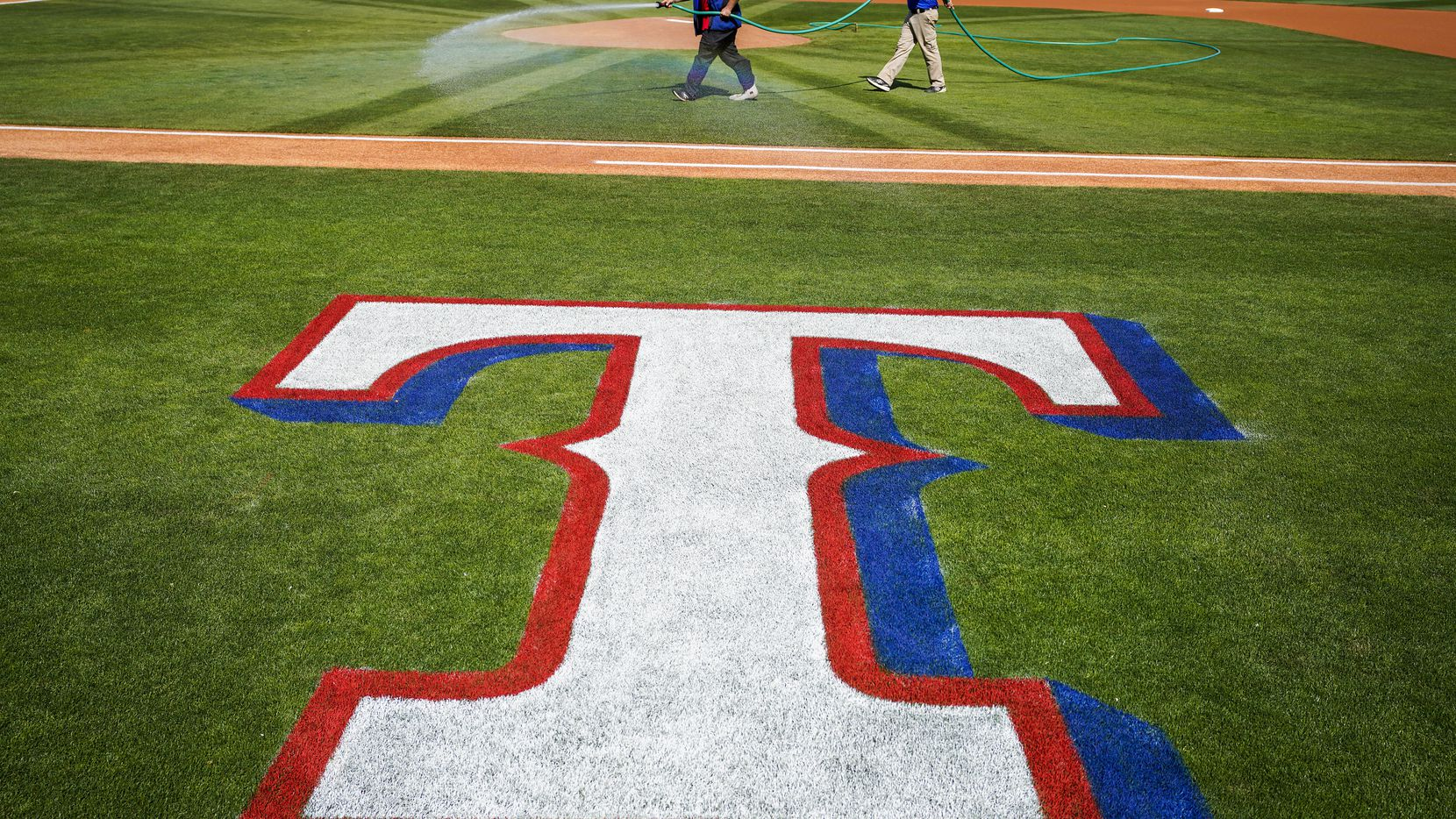FILE - Groundskeepers prepare the field before a spring game between the Rangers and Kansas City Royals at Surprise Stadium on Friday, Feb. 21, 2020, in Surprise, Ariz.