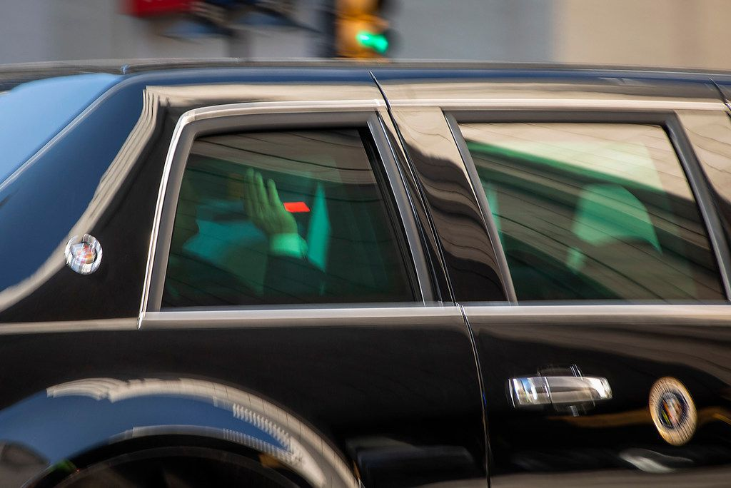 President Donald Trump waves from his motorcade along Commerce Street as he arrives at The Adolphus Hotel for a fundraiser on Thursday, May 31, 2018, in Dallas. (Smiley N. Pool/The Dallas Morning News)