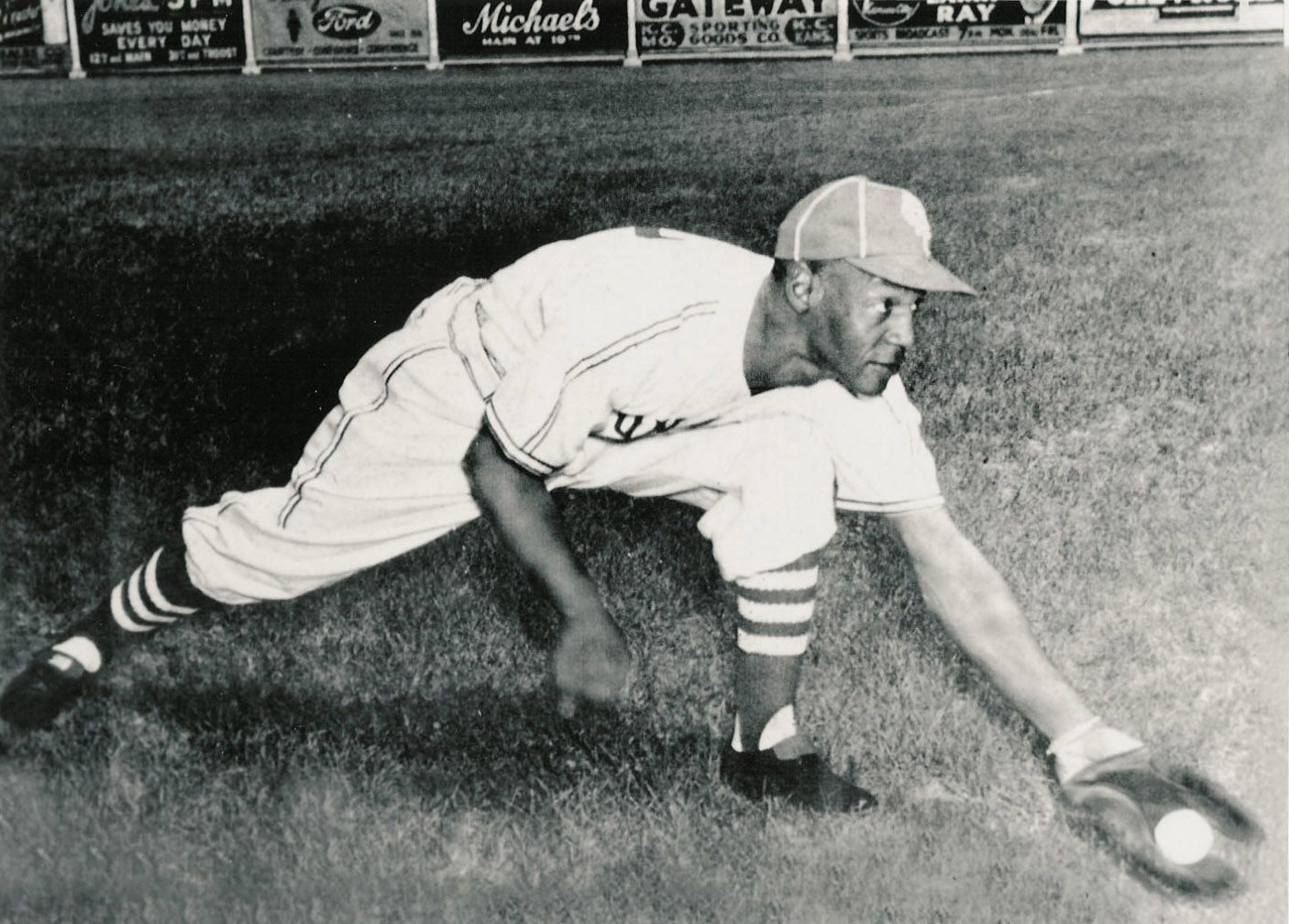 In this undated file photo released by the Negro Leagues Baseball Museum, Buck O'Neil catches a baseball.