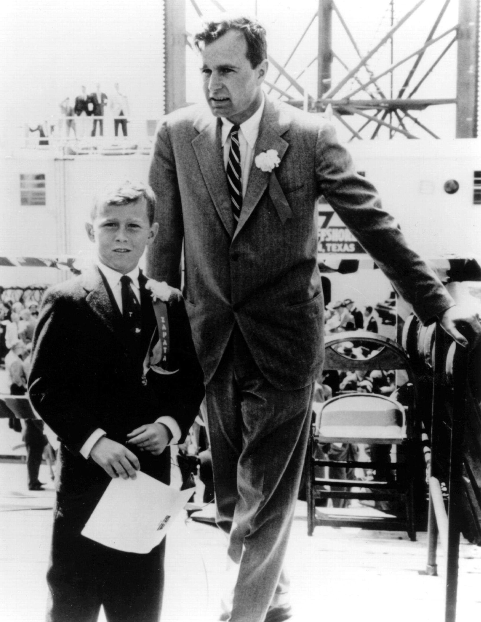 1956: George H.W. Bush and son George W. Bush at the commissioning ceremonies for the Scorpion off-shore drilling platform. Bush made a fortune drilling oil before entering politics.