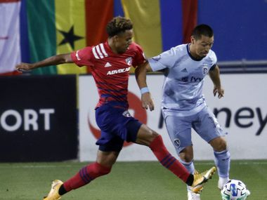 FC Dallas' Bryan Reynolds (14), left, challenges Sporting KC's Roger Espinoza (15) who works to maneuver the ball inside during first half action. The two teams, both members of the Western Conference of MLS, played their match at Toyota Stadium in Frisco on October 14, 2020.