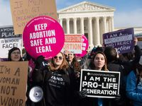 """Abortion rights supporters hold signs alongside abortion opponents participating in the """"March for Life,"""" an annual event to mark the anniversary of the 1973 Supreme Court case Roe vs. Wade, which legalized abortion in the US, outside the U.S. Supreme Court in Washington, D.C., on Jan. 18, 2019."""