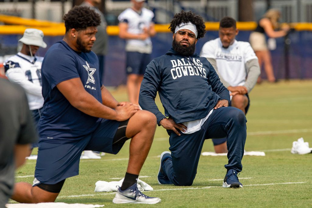 Dallas Cowboys offensive tackle La'el Collins, left and running back Ezekiel Elliott, right, do yoga for flexibility during NFL football training camp, Saturday, July 28, 2018, in Oxnard, Calif.