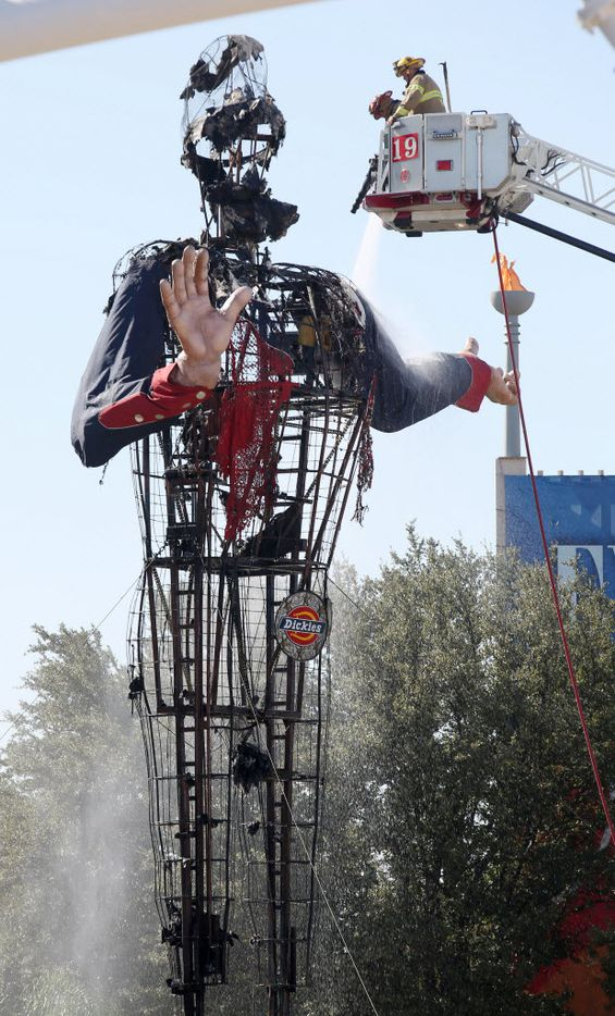 Dallas firefighters put out the last hot spots after Big Tex caught fire at the State Fair of Texas on October 19, 2012 in Dallas, TX.