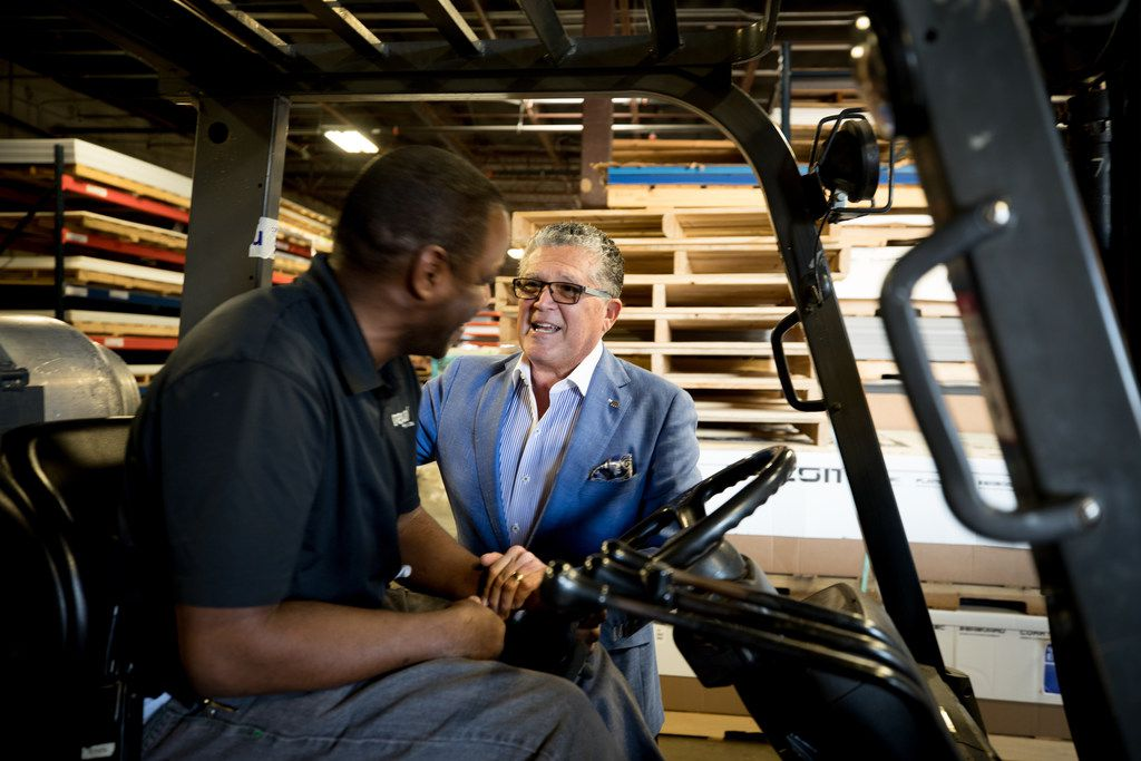 Wayne Gono, visionary/chief networking officer of Regal Plastics, talks to employee Vernon Mason. The Irving fabrication business uses wearable fitness trackers to help employees be healthier.