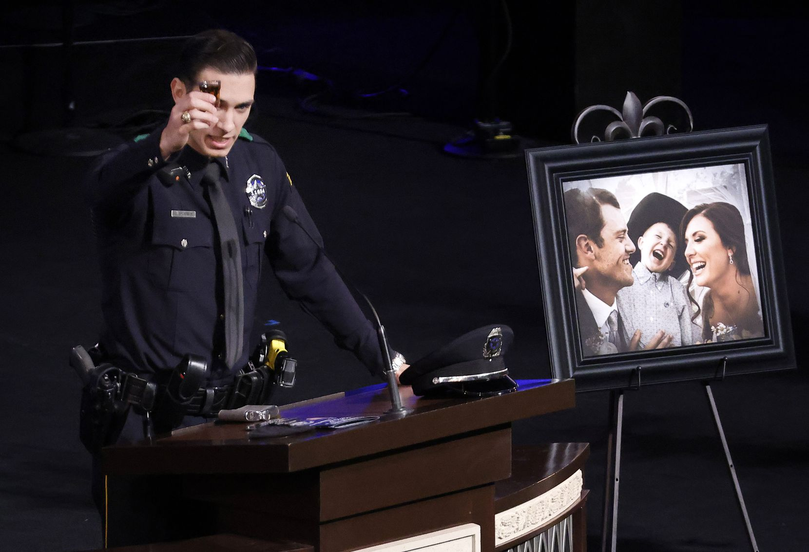 Dallas Police officer Colton Upchurch raises a shot glass of whiskey in his close friends name during the funeral service for Dallas Police officer Mitchell Penton at Prestonwood Baptist Church in Plano, Monday, February 22, 2021. The two were close friends from the time they met at recruit training. Upchurch still had an old flask of whiskey left in it from when they were together years ago. Penton was killed Saturday, Feb. 13, 2021, in a crash involving a drunk driving suspect.(Tom Fox/The Dallas Morning News)