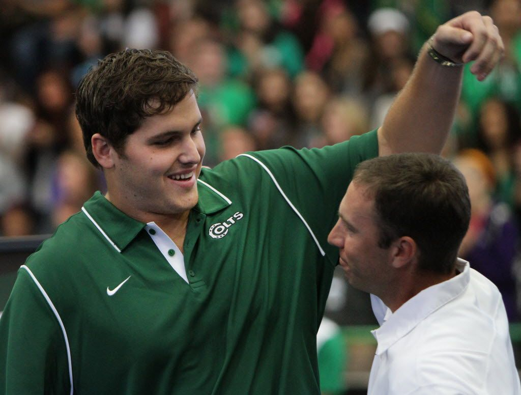 Luke Joeckel, first round drafft pick by the Jacksonville Jaguars, returned to Arlington High School, his alma mater, for a special recognition during a morning pep rally. Joeckel reaches to give his former head coach Scott Peach a hug after having his high school jersey retired before a capacity crowd assembled at the school gymnasium. (Steve Hamm/Special Contributor)