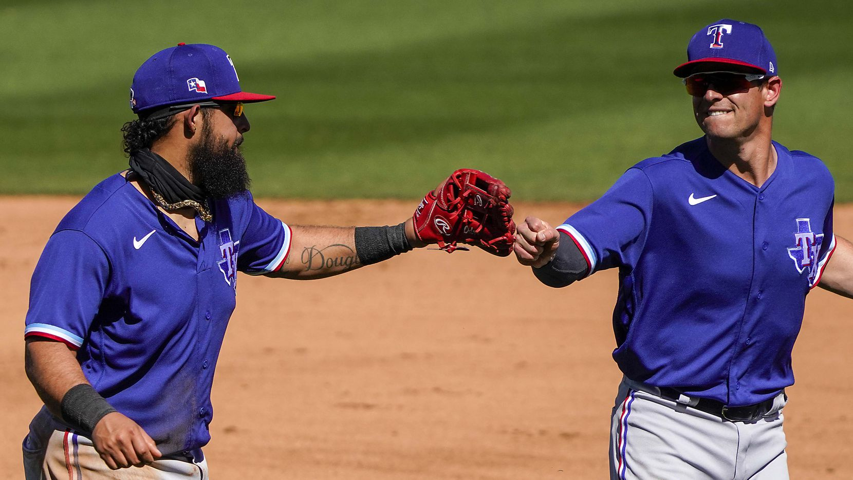 Texas Rangers third baseman Rougned Odor (left) celebrates with second baseman Nick Solak after Odor made a diving play during the fourth inning of a spring training game against the Arizona Diamondbacks at Salt River Fields at Talking Stick on Saturday, March 6, 2021, in Scottsdale, Ariz.