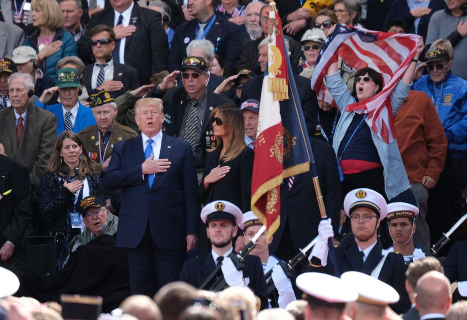 President Donald Trump joins in in singing the national anthem as First Lady Melania Trump looks on at the main ceremony to mark the 75th anniversary of the World War II Allied D-Day invasion of Normandy.