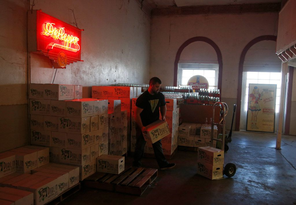 An old Dr Pepper neon sign shines as Cory Barbee moves cases of Dublin Bottling Works sodas to the soda shop next door. Dr Pepper is no longer bottled by the company, but a variety of new flavors have been introduced. (Guy Reynolds/The Dallas Morning News)