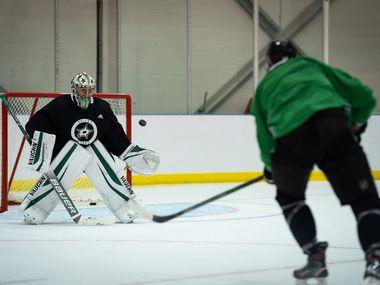 Goalie Anton Khudobin blocks a shot from Jason Dickinson as the Dallas Stars work out in their 'bubble' in Edmonton, in Alberta, Canada, on July 28, 2020.