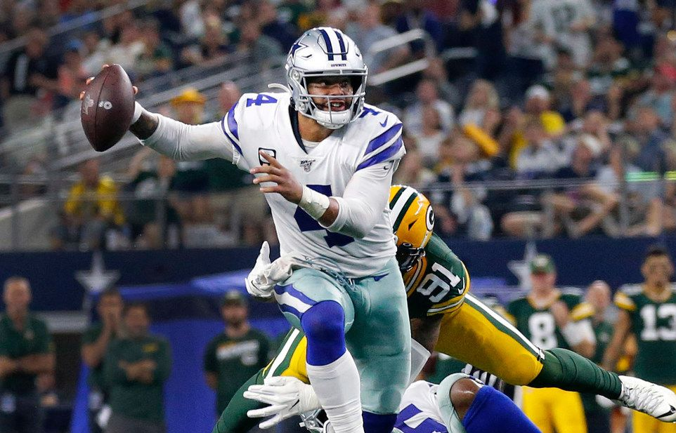 FILE - Cowboys quarterback Dak Prescott (4) eludes Packers defenders during the fourth quarter of a game at AT&T Stadium in Arlington on Sunday, Oct. 6, 2019.