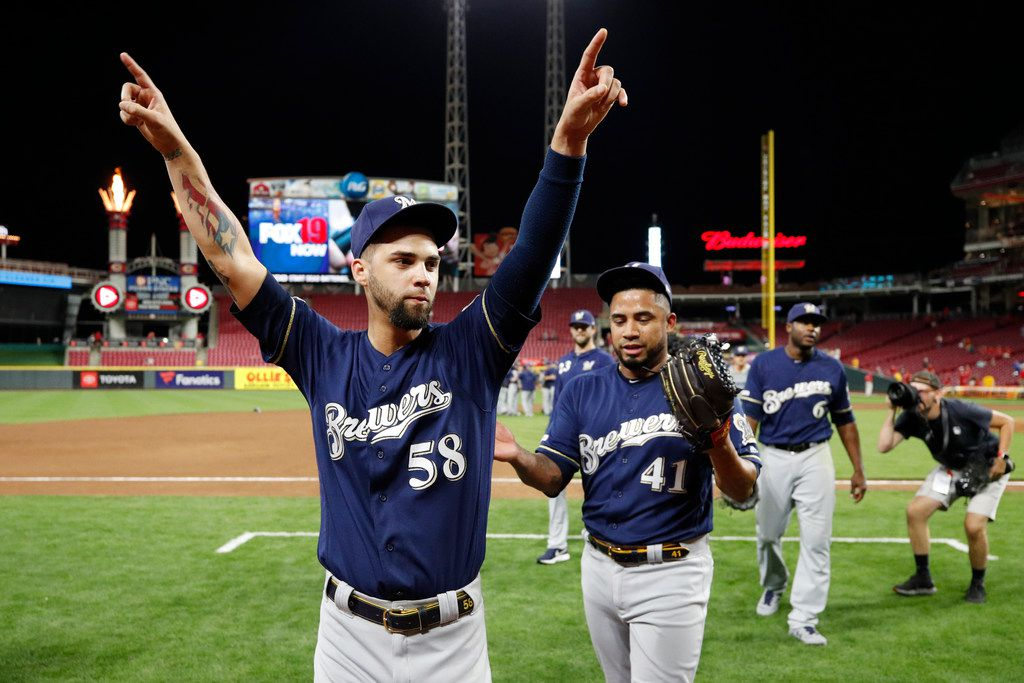 CINCINNATI, OH - SEPTEMBER 25: Alex Claudio #58 and Junior Guerra #41 of the Milwaukee Brewers celebrate after clinching a playoff berth following a 9-2 win over the Cincinnati Reds at Great American Ball Park on September 25, 2019 in Cincinnati, Ohio. (Photo by Joe Robbins/Getty Images)