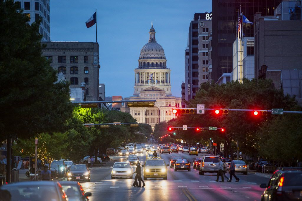 The Texas State Capitol building stands past cars and pedestrians crossing the street at dusk in Austin, Texas, U.S., on Saturday, April 4, 2015. Photographer: Matthew Busch/Bloomberg