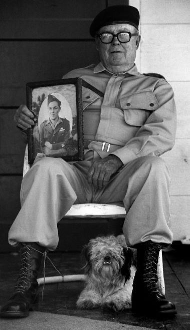 World War II veteran Ernest Raxter holding a 1944 picture of himself.  He is flanked by his dog Scotty as they sit outside Raxter's home in Athens, Texas.  Photograph published on May 29, 1994.