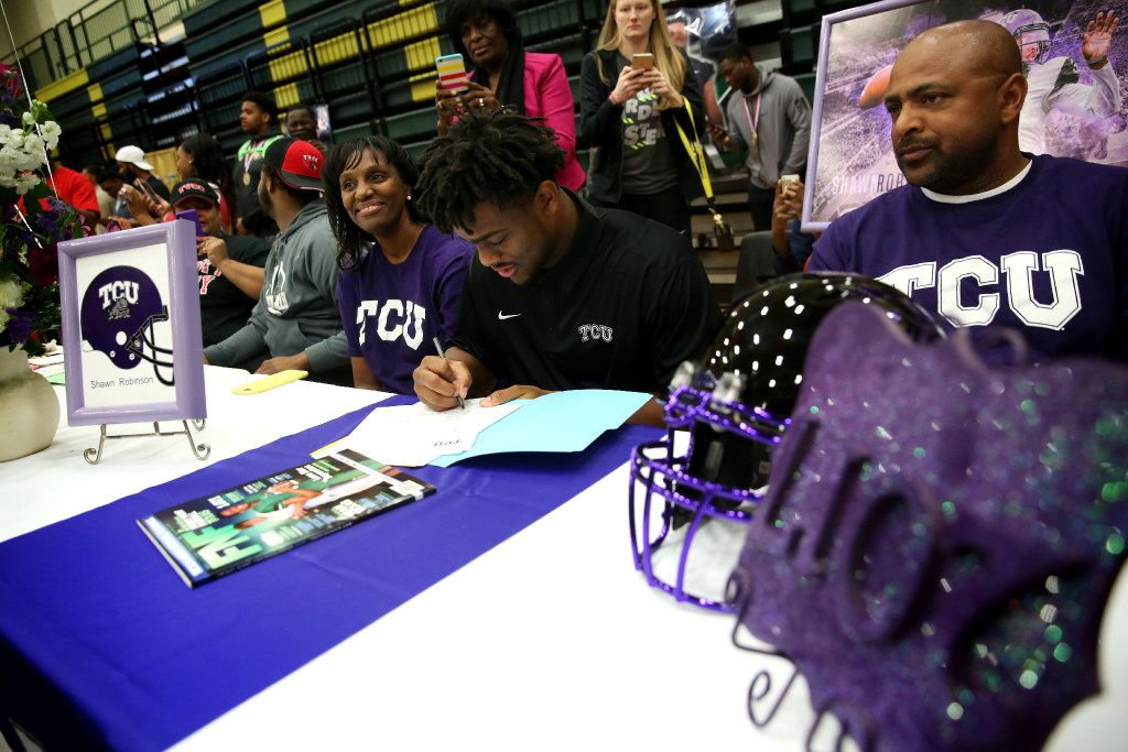 Quarterback Shawn Robinson signs with TCU, alongside his parents Andrea and Othell Robinson during national signing day at DeSoto High School in DeSoto, Texas on Wednesday, Feb. 1, 2017. DeSoto had 29 athletes, including 28 football players, sign with their college of choice. (Rose Baca/The Dallas Morning News)