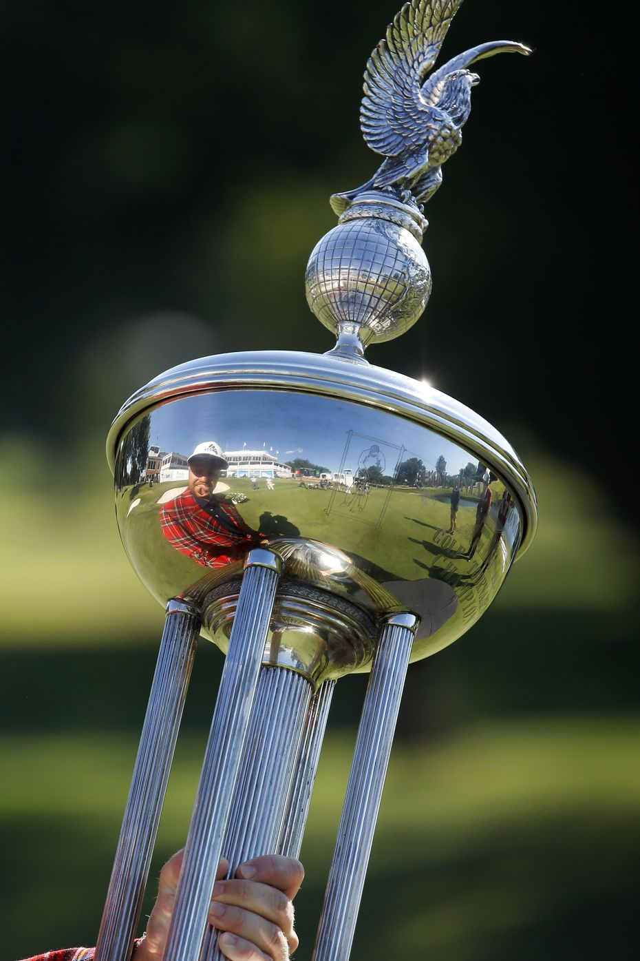 On the 18th green, PGA Tour golfer Daniel Berger looks at himself reflected in the winning Leonard Trophy after defeating Collin Morikawa in a one-hole playoff in the final round of the Charles Schwab Challenge at the Colonial Country Club in Fort Worth, Sunday, June 14, 2020.