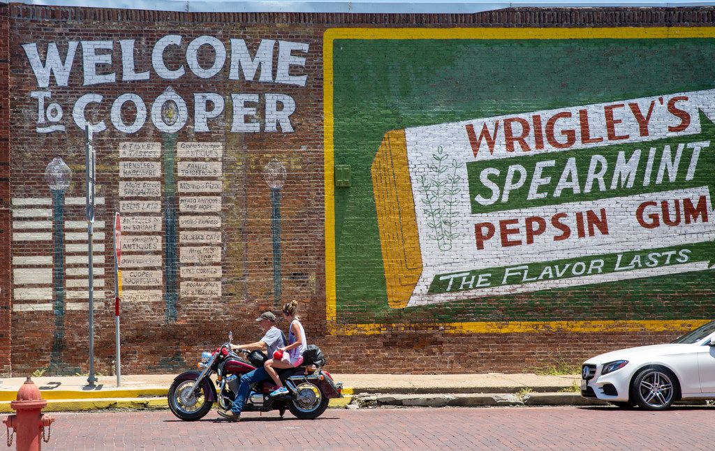 "A motorcyclist passes by a signature landmark of Cooper, Texas, on Thursday, July 11, 2019. The Texas Department of Banking closed the town's Enloe State Bank in late May, citing ""insider abuse and fraud by former officers."""