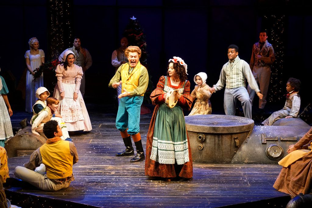 """Brian Mathis is Mr. Fezziwig (center left), Young Scrooge's boss, and Sarah Gay is Mrs. Fezziwig (center right) in Dallas Theater Center's """"A Christmas Carol"""" at the Wyly Theatre."""