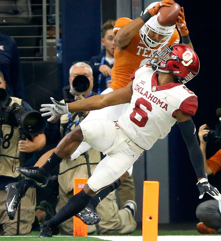 Texas Longhorns wide receiver Collin Johnson (9) comes down with a touchdown pass behind Oklahoma Sooners cornerback Tre Brown (6) in the third quarter of the Big 12 Championship at AT&T Stadium in Arlington, Texas, Saturday, December 1, 2018. The Sooners defeated the Longhorns, 39-27. (Tom Fox/The Dallas Morning News)