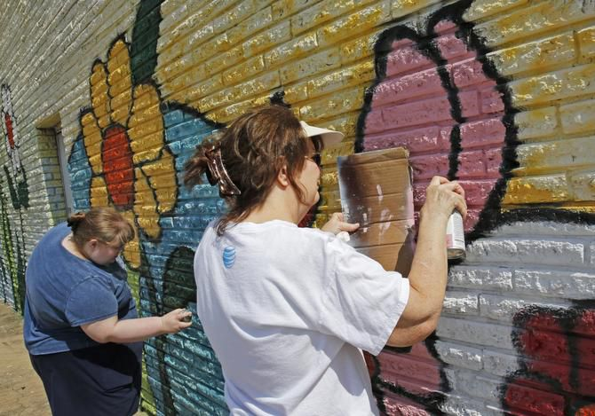 Dawn Lavender (left) and her mother, Melanie Richardson, joined other local artists touching up murals and adding a new one at Park Plaza Shopping Center in east Arlington in this 2014 file photo. A new program is encouraging residents to head downtown to see outdoor murals in the city center.