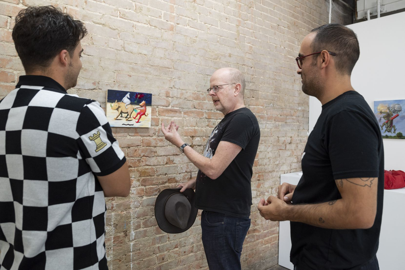 """Artist and collector Ludwig Schwarz (center) speaks with gallery owner Kevin Rubén Jacobs (left) and artist Francisco Moreno about a piece titled """"Three Amigos,"""" which will be on view at Olivier François Galerie through Sept. 4."""
