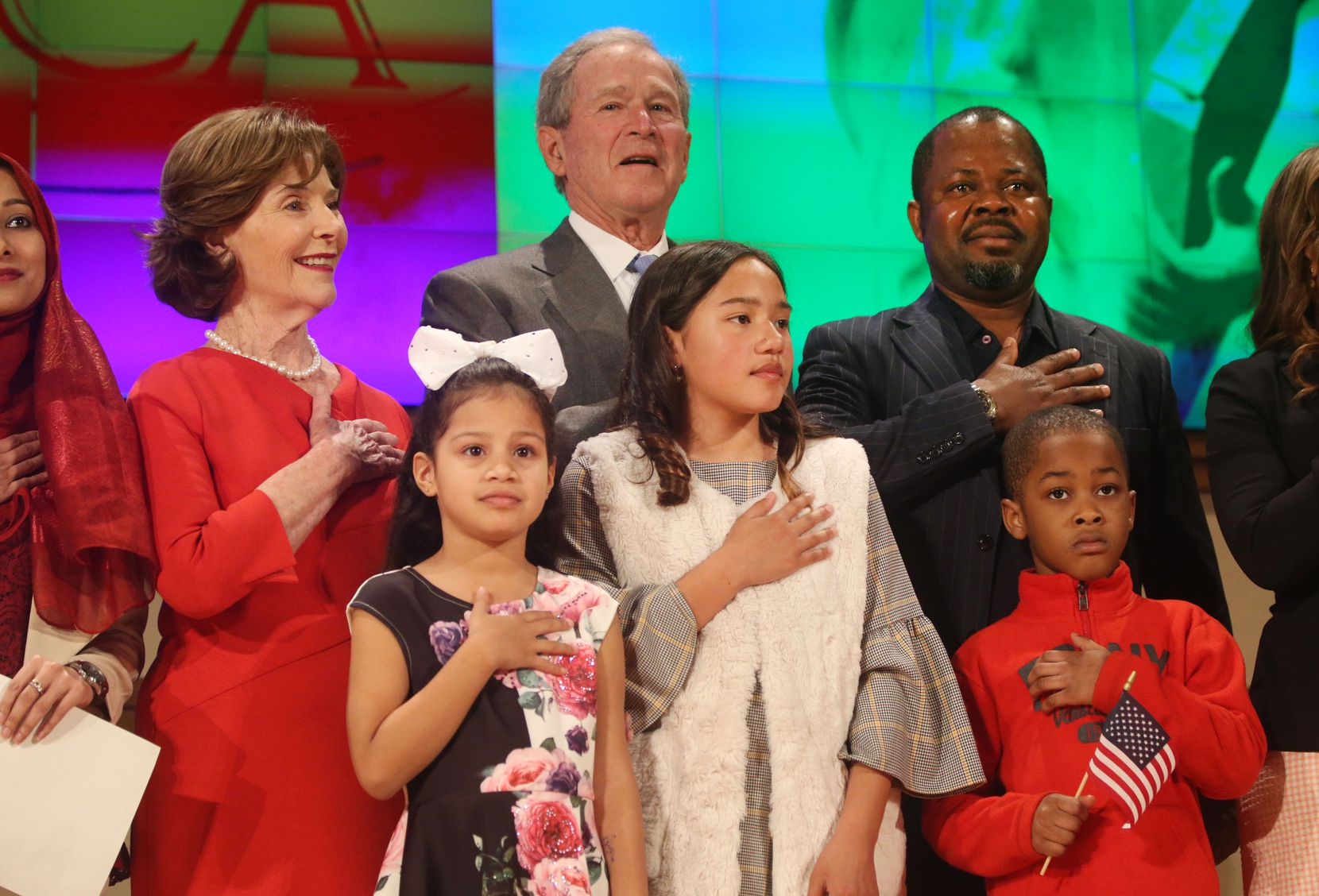Former President George W. Bush and former first lady Laura Bush recite the pledge of allegiance with new U.S. citizens, including Felix Odeh, (top right) of Nigeria, during a naturalization ceremony at the George W. Bush Presidential Center in Dallas on Monday, March 18, 2019.
