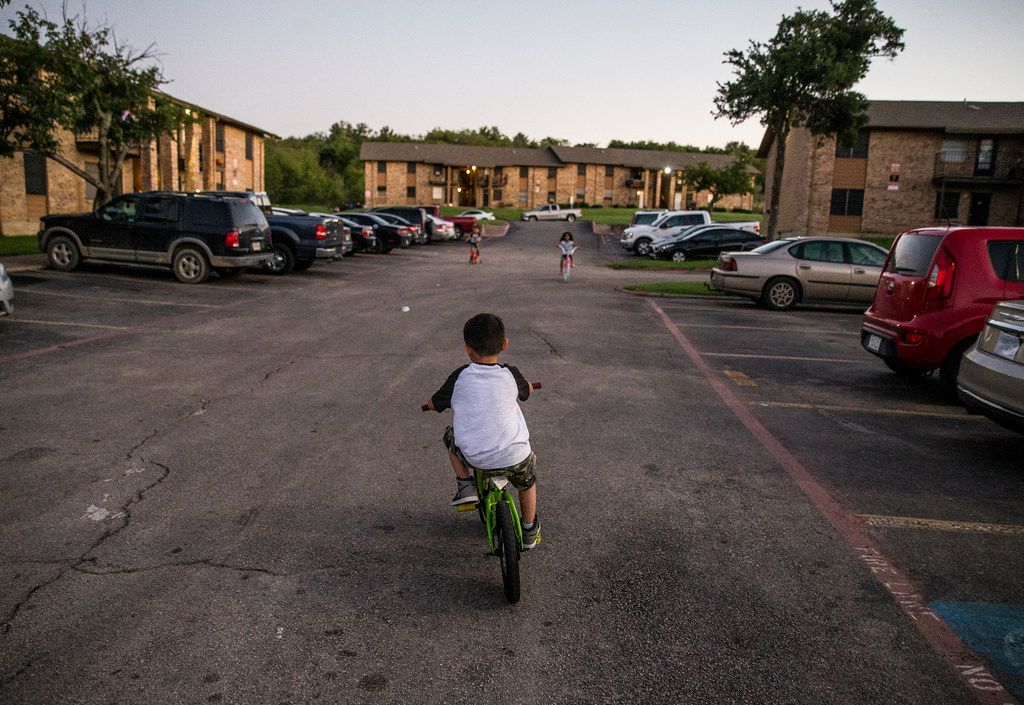 Isaac Guevara, 7, plays on his bike in front of his home at the Mountain View Apartments in Dallas.