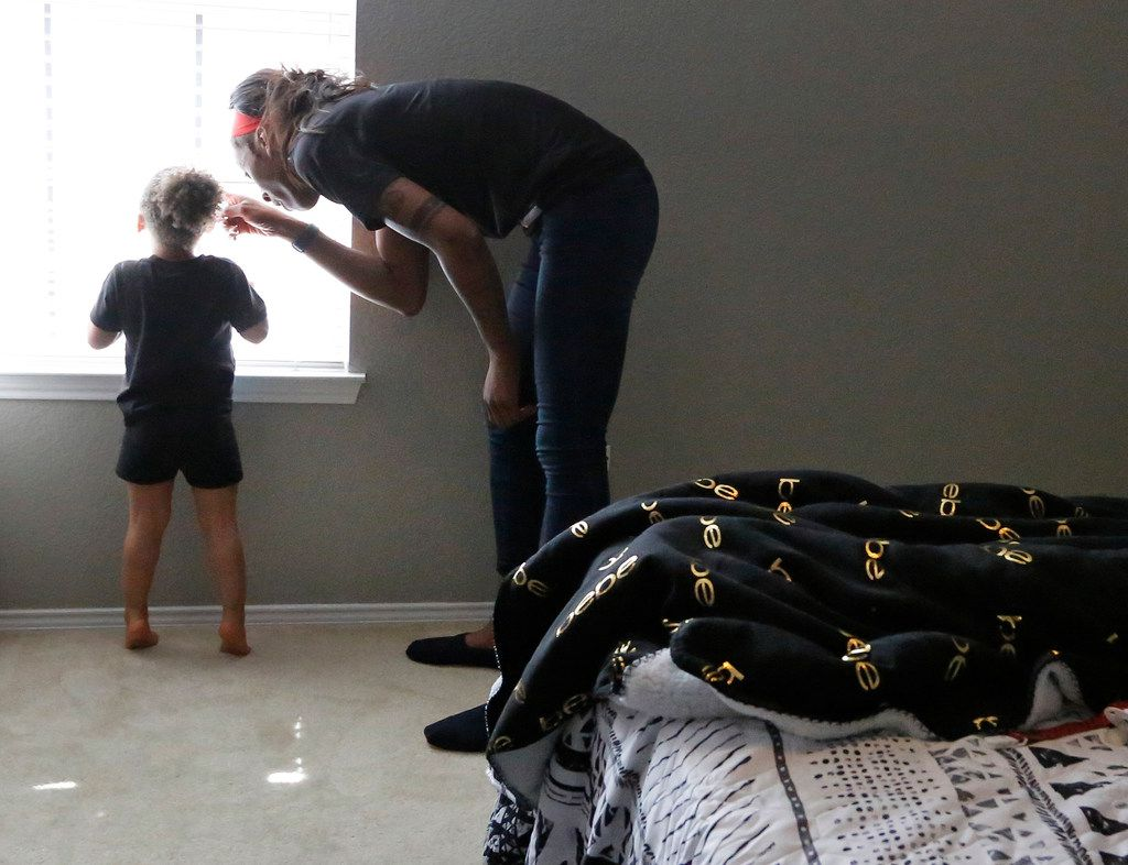 Dallas Wings' player Glory Johnson shows her daughter where the dogs are in the yard through the bedroom window at their home in Arlington, Texas, on Saturday, June 30, 2018. (Louis DeLuca/The Dallas Morning News)