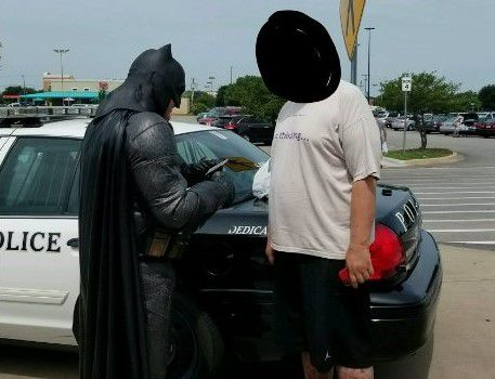 Officer Damon Cole, dressed as Batman, gives a citation to a man accused of shoplifting at Wal-Mart.