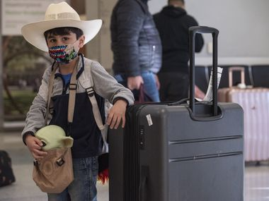Israel Valles, 5, holds on to his baby Yoda toy while waiting for his father as his family returned from San Luis Potosi, Mexico, at DFW International Airport in Dallas, on Tuesday, Jan. 26, 2021.