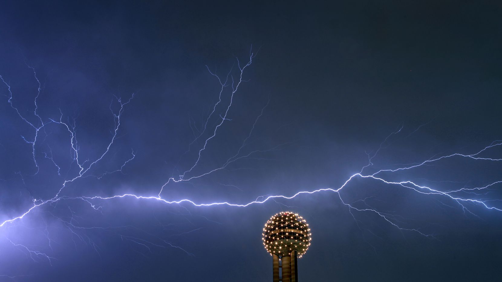 Lightning streaks across the sky behind the Reunion Tower Ball in downtown Dallas Thursday night, Sept. 29, 2011. (AP Photo/Brad Loper - The Dallas Morning News)