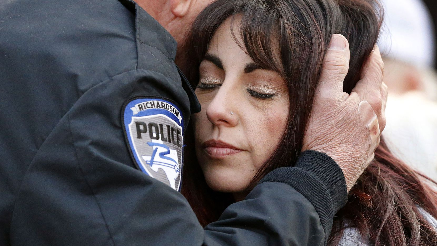 Richardson police chief Jimmy Spivey hugs Nicole Sherrard, wife of slain Richardson police officer David Sherrard, after Spivey spoke during a vigil for Sherrard in Richardson, Texas, Sunday, February 11, 2017.