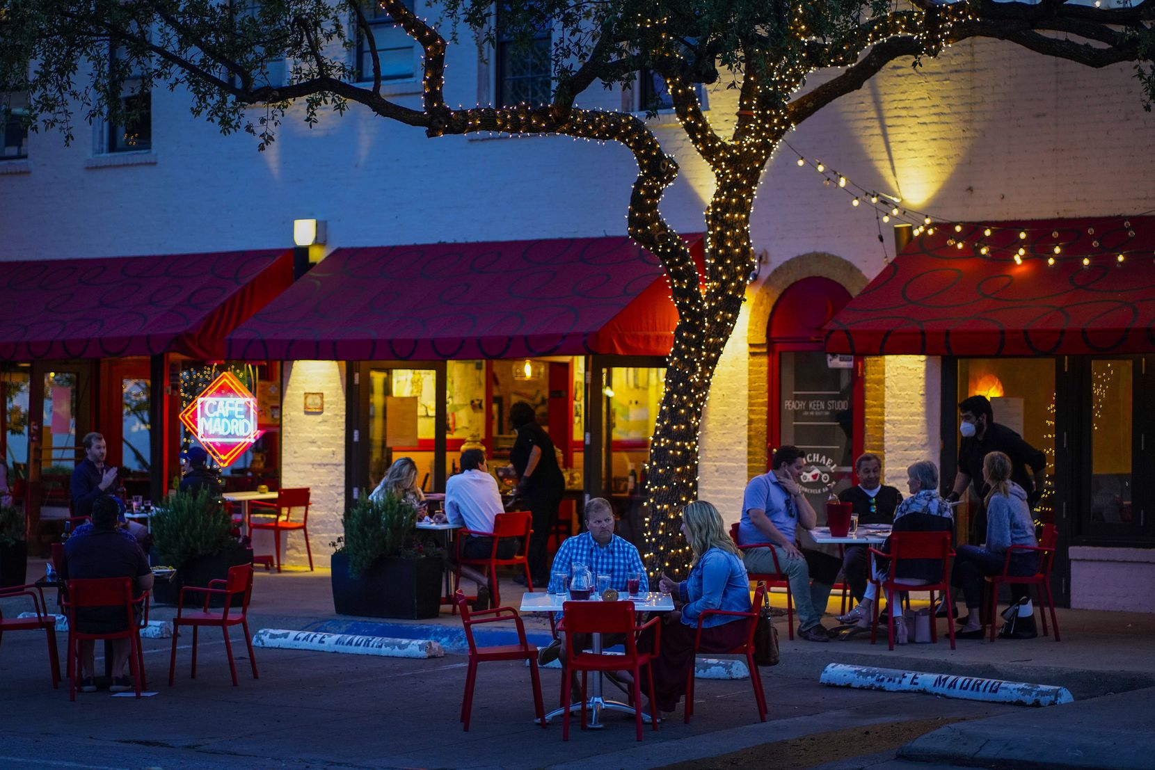 Patrons had dinner on tables spread out into the parking spaces in front of Cafe Madrid on Travis Street in Dallas on May 8, 2020. With restaurants offering dine-in services restricted to 25% occupancy and parties seated at least 6 feet apart, the restaurant expanded seating into the parking area.