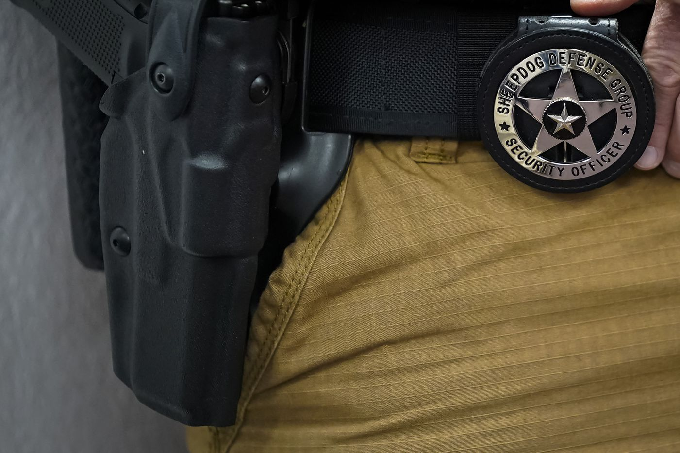 A participant wears a badge signifying they have met the organization's security officer requirements during a Sheepdog Defense Group armed security programs church safety training at Cornerstone Community Church on Sunday, Feb. 2, 2020 in Springtown, Texas.