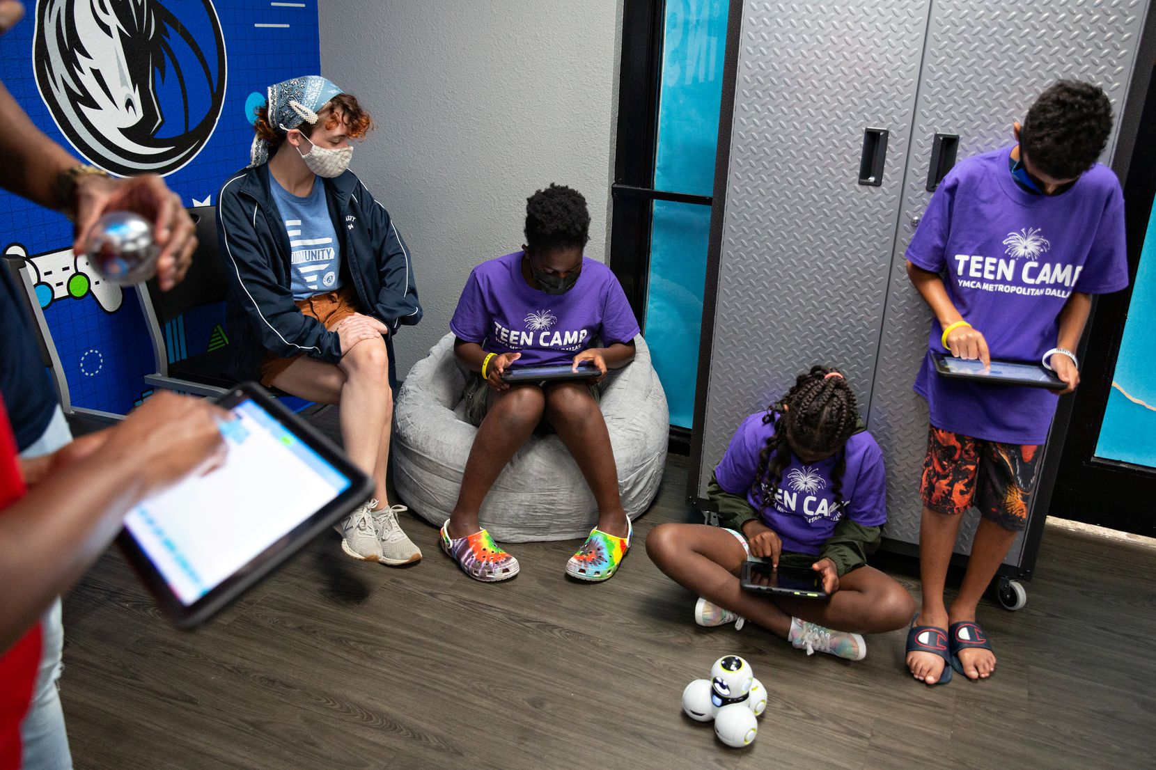 YMCA teen camp counselor Hannah McClellan watches Heaven Tell, 12, Deknea Witherspoon, 11, and Ishmael McNeil, 12, play with iPads and robotics at the Mavs Foundation's unveiling of its newest reading and earning center renovation at the Moorland YMCA at Oak Cliff on August 3, 2021. (Shelby Tauber / Special Contributor)