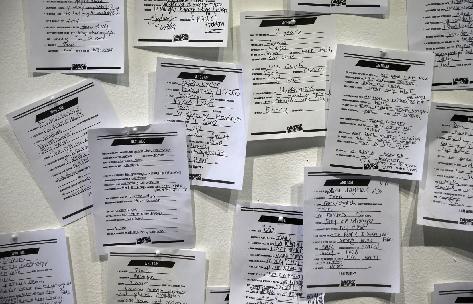 Participants in DaVerse Lounge's performances fill out at response templates, which are pinned to a wall in the Life in Deep Ellum building in Dallas as part of an exhibit of the project's work.