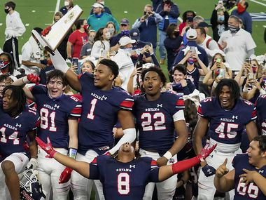 Denton Ryan's Ja'Tavion Sanders (1) hoists the championship trophy as players celebrate a 59-14 victory over Cedar Park to win the Class 5A Division I state football championship game at AT&T Stadium on Friday, Jan. 15, 2021, in Arlington, Texas. (Smiley N. Pool/The Dallas Morning News)