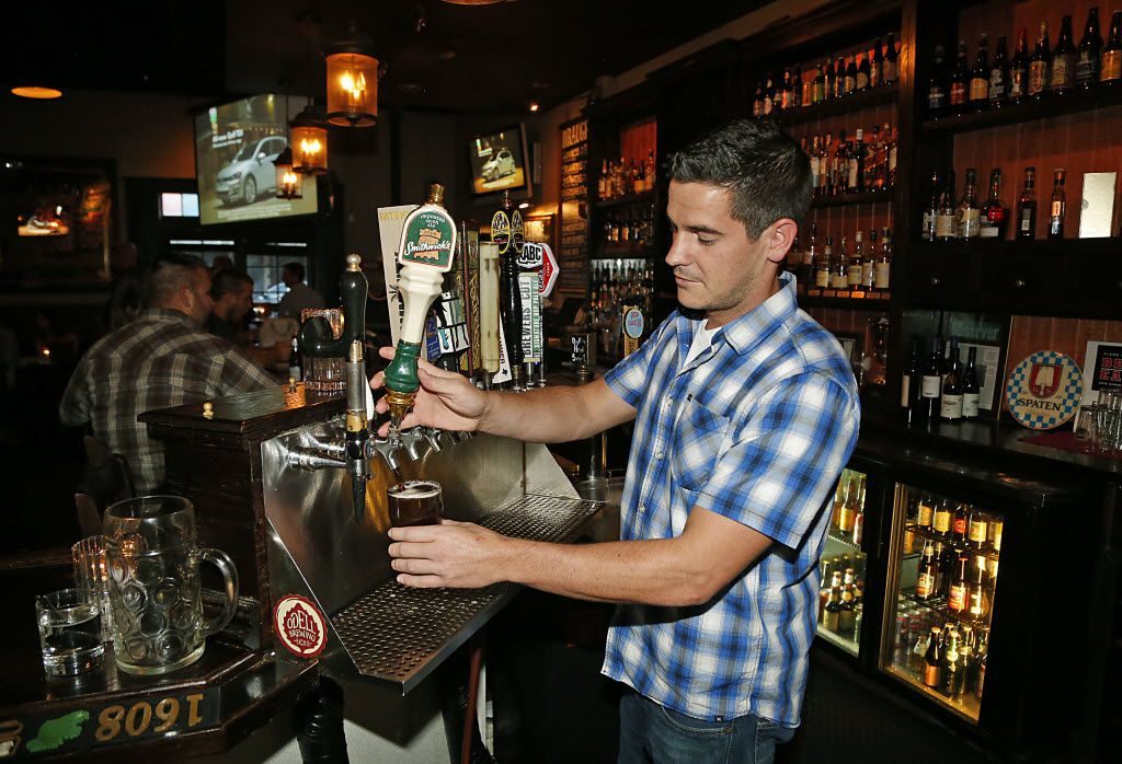 Jarrod Smith of Plano, a bartender at the Fillmore Pub in Plano, pours a draught beer on Thursday night, September 4, 2014.