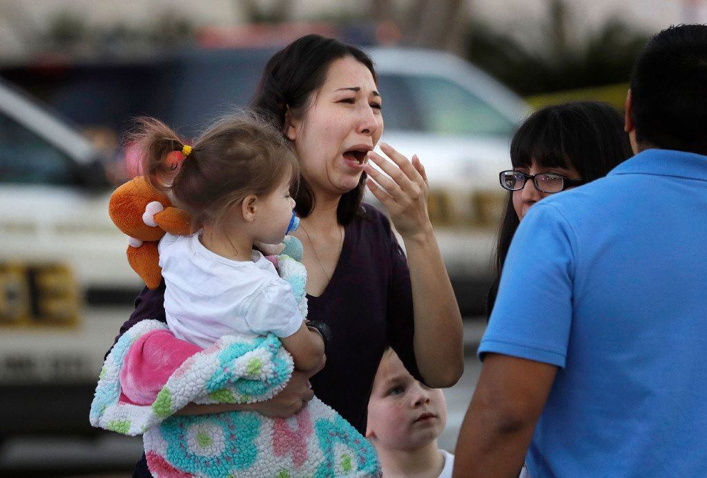 A woman holds her child after San Antonio police helped her and other shoppers exit the Rolling Oaks Mall.