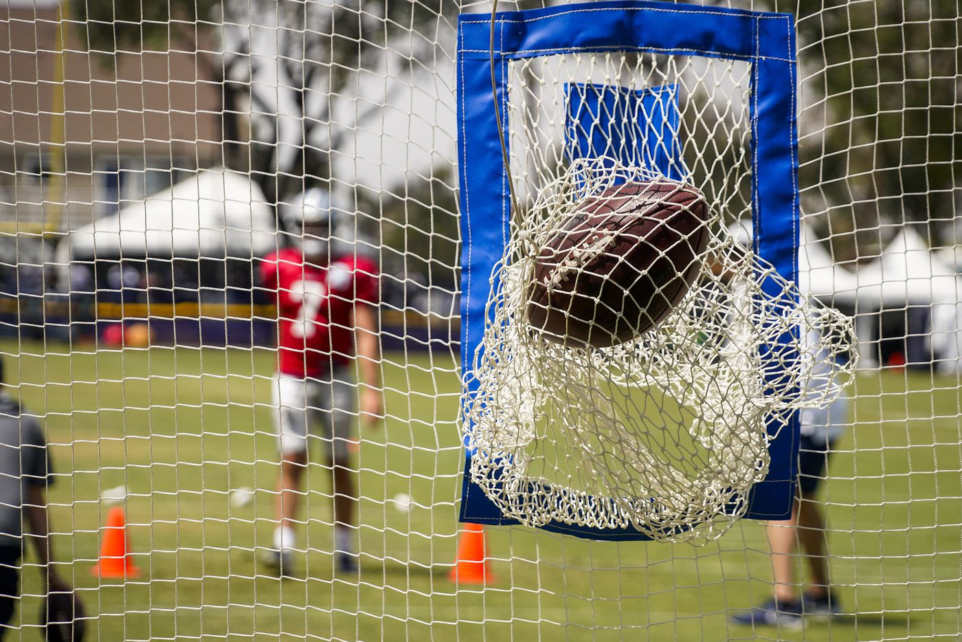 A pass by Dallas Cowboys quarterback Ben DiNucci (7) rips a target net during a practice at training camp on Wednesday, July 28, 2021, in Oxnard, Calif.