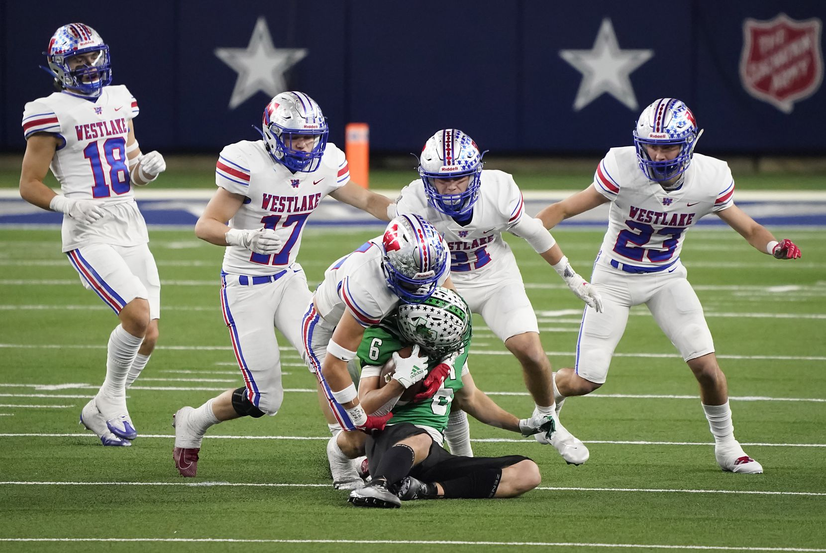 Southlake Carroll wide receiver Landon Samson (6) is brought down by Austin Westlake defensive back Michael Taaffe (14) as defensive back Ford Dickerson (18), linebacker Brady Lamme (17), defensive back Carter Barksdale (21) and defensive back Beau Breathard (23) close in on the play during the second quarter of the Class 6A Division I state football championship game at AT&T Stadium on Saturday, Jan. 16, 2021, in Arlington, Texas.