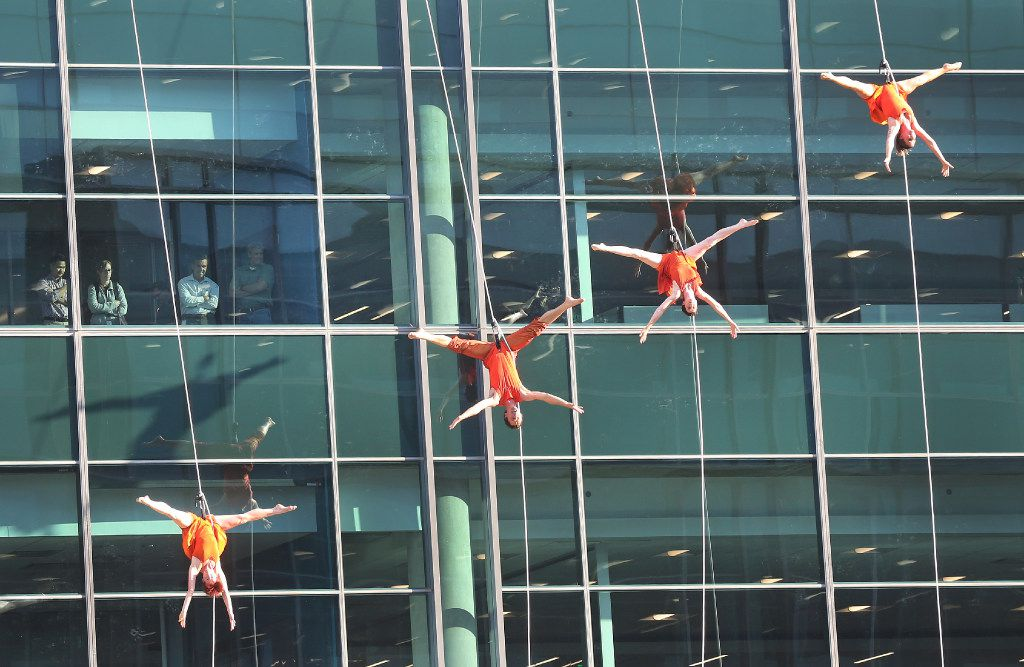Aerial dancers perform on the Toyota building, as employees watch from their office windows, at the grand opening ceremony of the Toyota headquarters in Plano, Texas, photographed on Thursday, July 6, 2017. (Louis DeLuca/The Dallas Morning News)