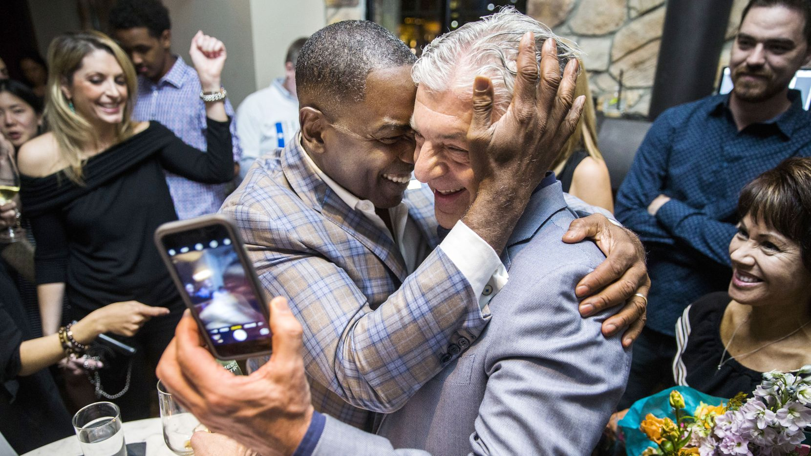 Plano mayoral incumbent Harry LaRosiliere, center left, hugs Fehmi Karahan after the majority of polls reported in his favor at an election night campaign party on Saturday, May 6, 2017 at Mexican Sugar restaurant in Plano.