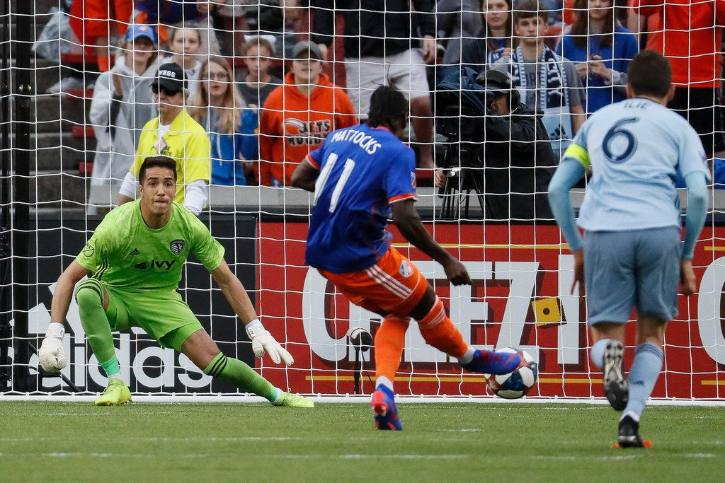 FC Cincinnati forward Darren Mattocks (11) scores against Sporting Kansas City goalkeeper Adrian Zendejas, left, on a free kick during the first half of an MLS soccer match Sunday, April 7, 2019, in Cincinnati. (AP Photo/John Minchillo)