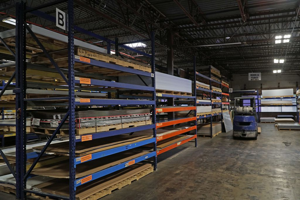 Raw material is stacked floor to ceiling at Regal Plastics in Irving. The company is selling millions of dollars of plastic barriers and guards.