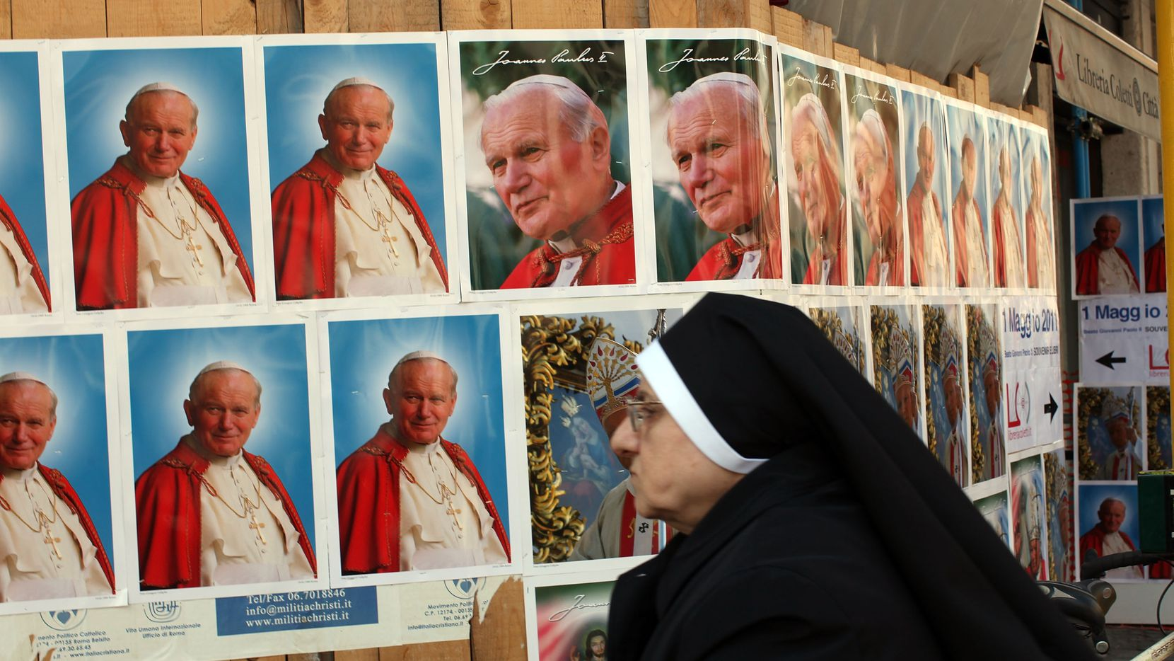 Una monja observa rótulos con la imagen del Papa Juan Pablo II, durante las ceremonias de beatificación en abril de 2011 en El Vaticano.