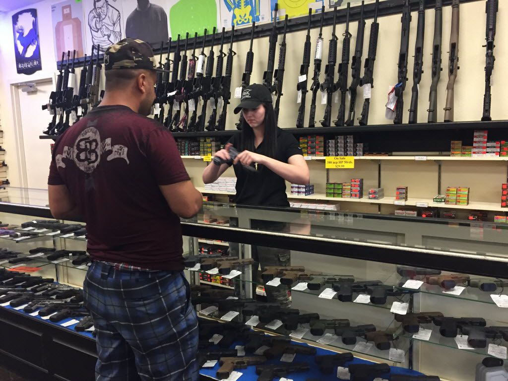 Holly Bohrer (right) readies a pistol for Omar Omar at the Gun Zone in Mesquite.
